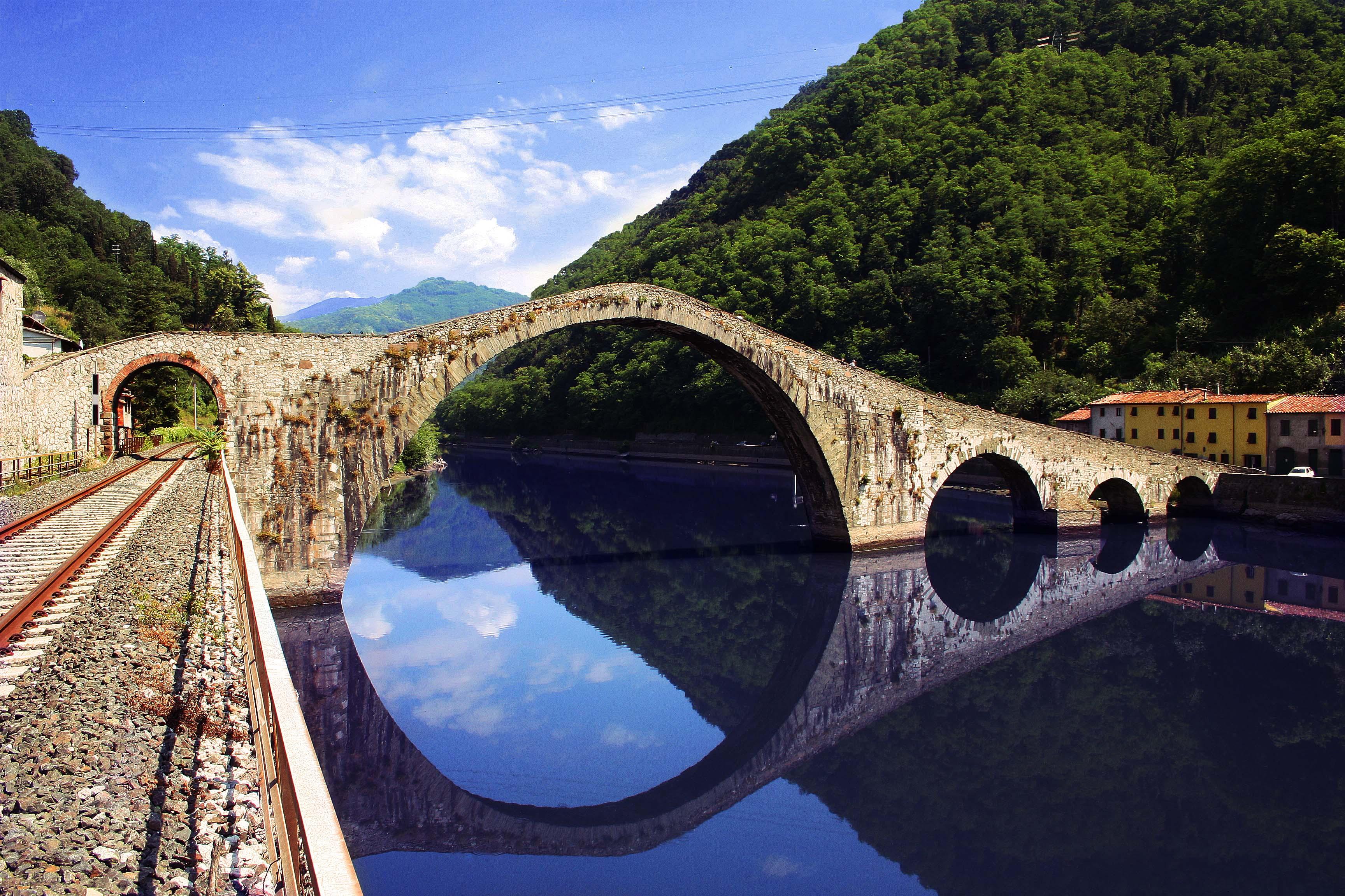 """Il ponte della Maddalena unisce le due sponde del fiume Serchio all'altezza del paese di Borgo a Mozzano. La sua costruzione risale ai tempi della Contessa Matilde di Canossa (1046-1115), che ebbe grossa influenza e potere su questa zona della Toscana, la Garfagnana, ma il suo aspetto attuale è dovuto alla ricostruzione effettuata da Castruccio Castracani (1281-1328), condottiero e signore della vicina Lucca, nei primi anni del 1300. L'aspetto del ponte è quello medievale classico a 'schiena d'asino', con la differenza, che qui diventa caratteristica unica, che le sue arcate sono asimmetriche e quella centrale è talmente alta e ampia che la sua solidità sembra una sfida alla legge di gravità. Il ponte è comunemente chiamato 'del Diavolo' in forza di una leggenda popolare della zona, rinforzata dall'aspetto scombinato del ponte: un capo muratore aveva iniziato a costruirlo ma ben presto si accorse che non sarebbe riuscito a completare l'opera per il giorno fissato e preso dalla paura delle possibili conseguenze si rivolse al Maligno chiedendo aiuto al fine di terminare il lavoro. Il Diavolo accettò di completare il ponte in una notte in cambio dell'anima del primo passante che lo avesse attraversato. Il patto fu siglato ma il costruttore, pieno di rimorso, si confesso con un religioso della zona che lo consigliò di far attraversare il ponte per primo ad un porco. Il Diavolo fu così beffato e scomparve nelle acque del fiume. La foto, che ha partecipato al concorso PREMIO DI FOTOGRAFIA """"Uno scatto di solidarietà"""" indetto da """" La Venerabile Arciconfratenita della Misericordia di Firenze"""", si è classificata al secondo posto: premiazione avvenuta il 22/05/2010."""